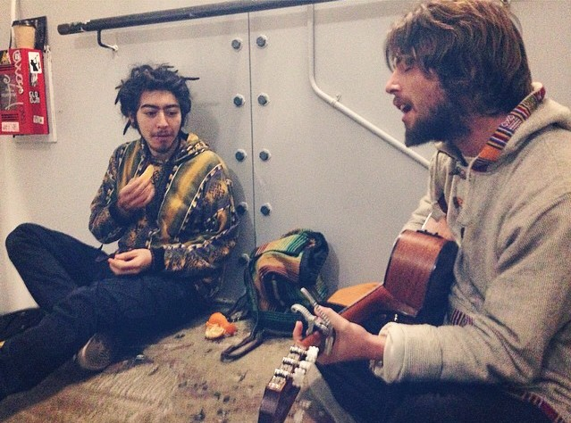 Sam Garrett (right) performing his songs in a stairwell in Camden, and his friend Jonny Gonzales (left). Image: Georgina Palzeaird