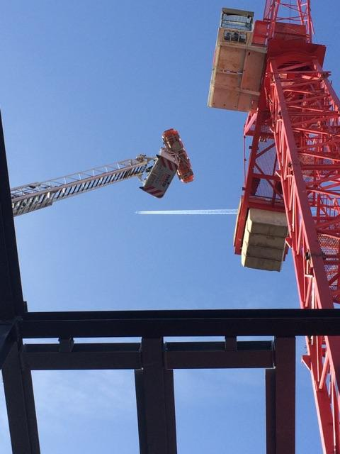 Dramatic rescue of crane driver taken ill in Putney. Ladder at its maximum height. Medic with firefighters. Image: @LFB