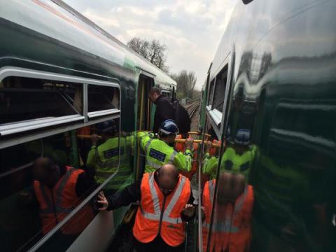 Passengers being helped onto another train after lorry crashes into rail bridge. Image@LFB