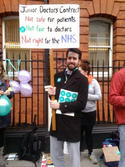 A junior doctor holding a placard supporting the strike action. Image: Al Riddell.