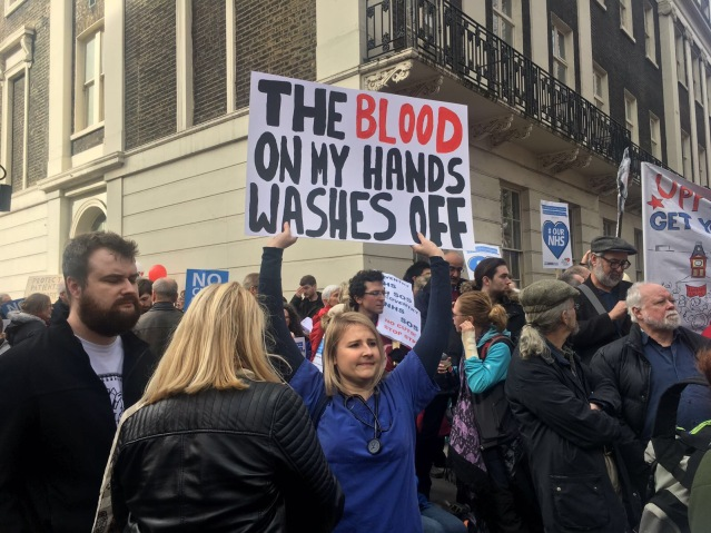 "A healthworker holds a sign which reads ""The blood on my hands washes off."""