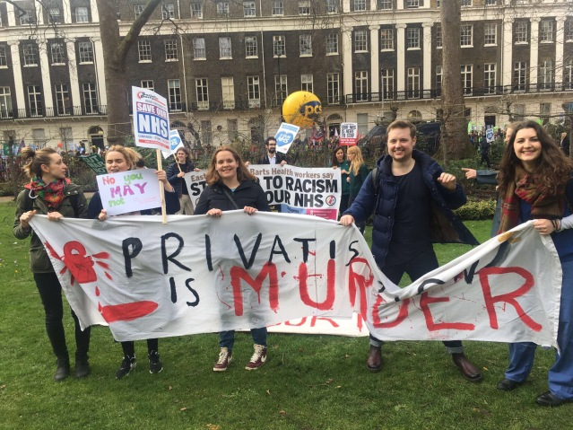 """Healthcare students hold a banner which reads """"Privatisation is murder."""""""